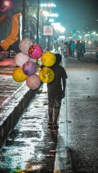 A poor child selling beautiful and colorful balloons on the street of Hyderabad to earn his living.