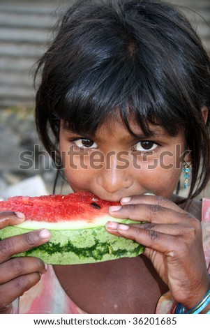 A poor & hungry girl from India eating a watermelon.