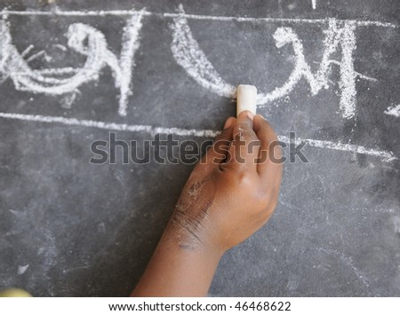 A poor kid in India learning to write alphabets.