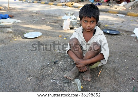 A poor kid in India, sitting on the streetside.