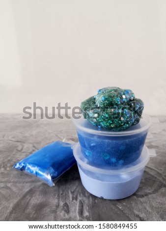 A popular trendy children's toy, homemade slime, bright blue, green clay with sparkles and balls on an abstract blurred background. For relaxation, hobbies and entertainment. #1580849455