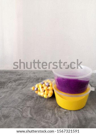 A popular trendy children's toy, homemade slime, bright yellow, purple clay, foam balls on an abstract blurred gray background. For recreation, hobbies and entertainment. #1567321591