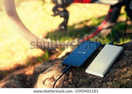 A portable charger charges the smartphone. Power Bank with cable against the background of wood and bicycle.