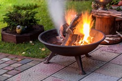A portable fireplace with bright burning firewood making sparks and smoke at the backyard  or garden near house. A place for evening meeting and stories.
