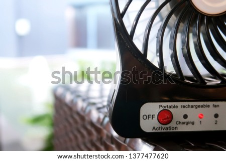 A portable rechargeable battery mini fan, working for cooling the heat temperature outdoor in the extremely hot summer day in Bangkok, Thailand #1377477620