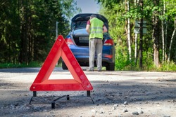 A portable, reflective red warning sign stands on the side of the road next to the damaged vehicle. A driver in a yellow vest is standing near the trunk. Selective focus.