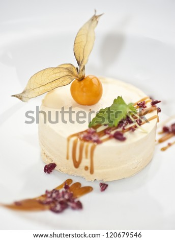 A portion of caramel parfait with a physalis and some mint on top