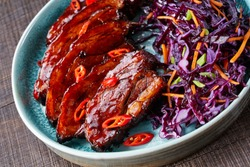 A portion of glazed pork belly char siu served on a blue plate with a salad of red cabbage and carrot, sprinkled with chili and spring onion on top, horizontal orientation, close-up