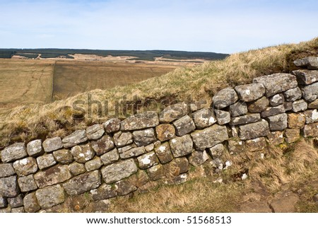 A portion of Hadrians Wall on an incline with the Northumbrian landscape in the distance