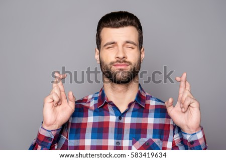 A portrair of a young man with crossed fingers and closed eyes praying for risky business Сток-фото ©