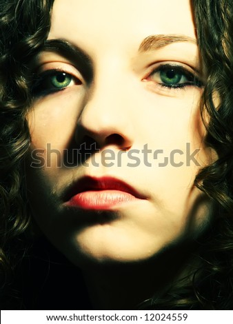 A portrait about a pretty lady with white skin, long brown wavy hair, green eyes and whose look is glamorous