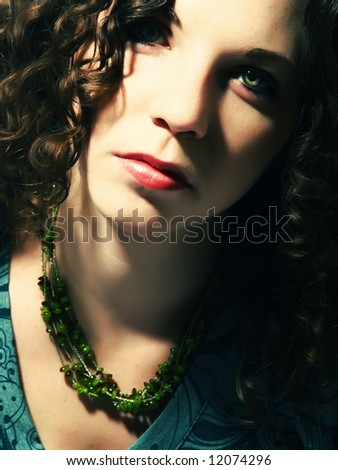 A portrait about a pretty lady with white skin, long brown wavy hair whose look is glamorous and she wears a nice green dress and necklace