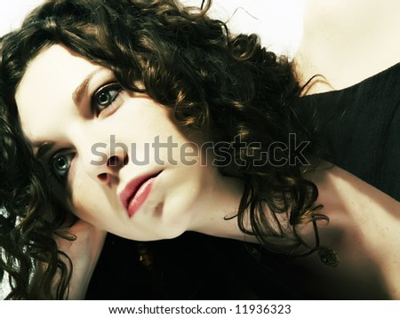 A portrait about an attractive lady with white skin and long brown wavy hair who wears a nice dark dress and she is thinking