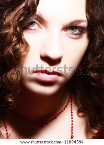 A portrait about an attractive woman with white skin and long brown wavy hair whose look is glamorous
