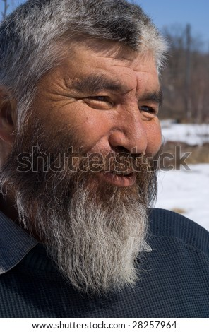 A portrait close up of the old men with grey beard. Small indigenous people of Russian Far East.
