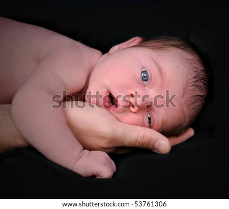 A portrait closeup of a newborn baby child in a father's hand on a black background with shadows. The baby has blue eyes and is staring into the camera.