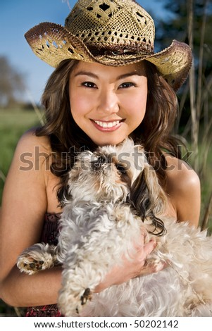 A portrait of a beautiful asian girl with her dog outdoor