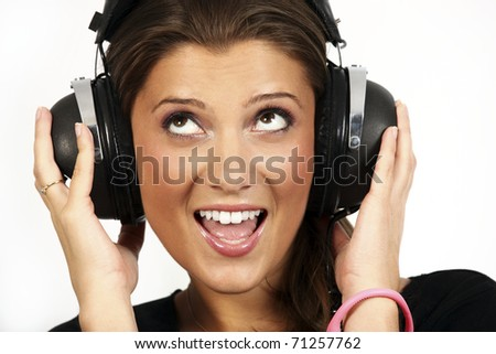 A portrait of a beautiful girl listening to music on her big headphones over white background