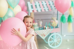 A portrait of a beautiful little girl smiles and holds in a hands a big color balloon in the studio with many balloons and a toy candy shop