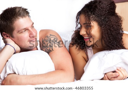 A portrait of a beautiful romantic interracial couple in love lying down on the bed
