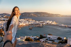 A portrait of a beautiful tourist woman who pulls the hand of her partner towards the town of Mykonos, Greece, during their summer vacation