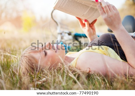 A portrait of a beautiful young Caucasian woman reading a book outdoor