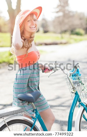 A portrait of a beautiful young Caucasian woman with her bike outdoor