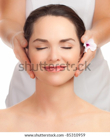 A portrait of a beautiful young woman getting a face massage