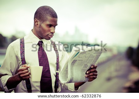 A portrait of a black businessman reading newspaper outdoor