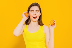 A portrait of a bright beautiful girl with a juicy grapefruit posing in the studio over the yellow background. Beauty, health.