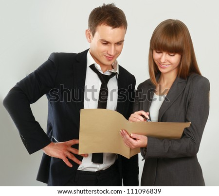 A portrait of a businesswoman and a businessman standing with folder on white background