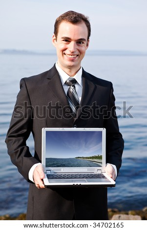 A portrait of a caucasian businessman holding a laptop outdoor (the image on the laptop was taken by me)
