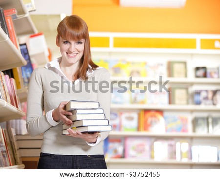 A portrait of a college student holding books in the library