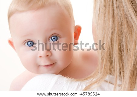 A portrait of a cute baby boy looking over his mothers shoulders.