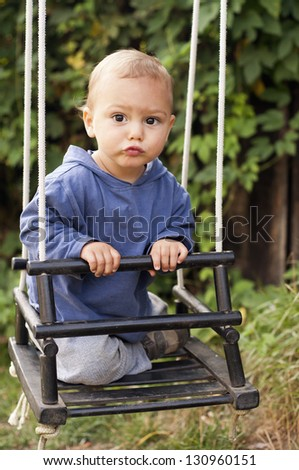 A portrait of a cute baby toddler or a small child, boy or girl, on a wooden  swing.