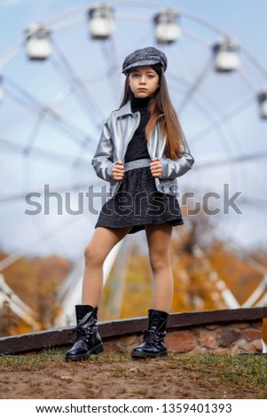 A portrait of a cute girl in a peaked hat with long hair outside  outside in autumn