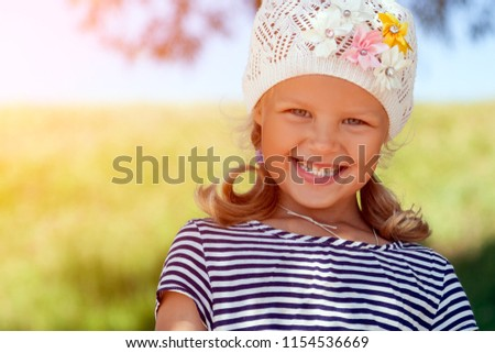 A portrait of a cute little girl who laughs and laughs happily in the park on a warm summer day. Concept of summer holidays at sea and live style