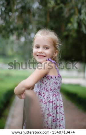 A portrait of a cute little girl who laughs and laughs happily in the park on a warm summer day. Concept of summer holidays at sea and live style #1548713474