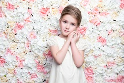 A portrait of a cute modest girl posing over the background with flowers. Beauty, fashion for kids.