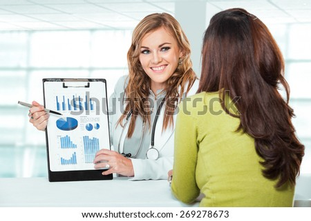 A portrait of a Doctor with female patient. Friendly, Happy Doctor with Stethoscope explaining to Patient in Clinic