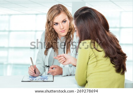 A portrait of a Doctor with female patient. Friendly, Happy Doctor with Stethoscope Giving Advice to Patient in Clinic