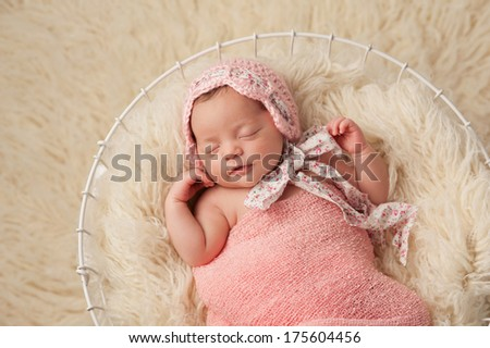 A portrait of a five week old newborn baby girl wearing a pink bonnet. She has a subtle smile and is peacefully sleeping in a wire basket.