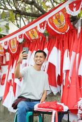 a portrait of a flag seller taking a photo selfie