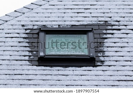 A portrait of a frozen slate roof with a skylight window which is also frozen during winter time. At the sides of the window the frost has molten because of bad isolation. Foto stock ©