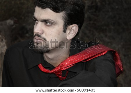 A portrait of a frustrated Indian executive wearing a stylish red tie and black shirt.