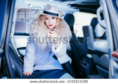 A portrait of a gorgeous bonde lady posing in a car. Car, fashion, beauty, chick.