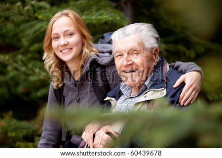 A portrait of a granddaughter and grandfather.  Shallow depth of field, focus on grandfather. - stock photo