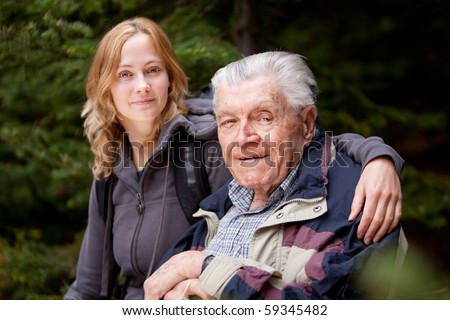 A portrait of a granddaughter with her grandfather in the forest