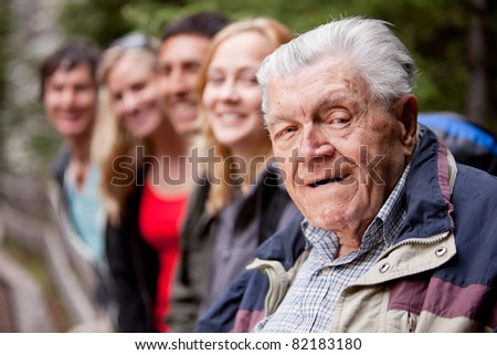 A portrait of a grandfather type man with a group of young people