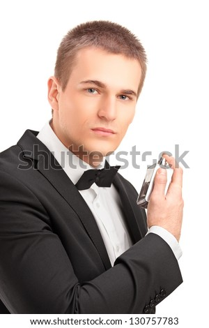 A portrait of a handsome male in black suit using parfume isolated against white background
